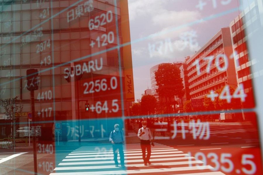 People wearing protective masks, following the coronavirus disease (Covid-19) outbreak, are reflected on a screen showing stock prices outside a brokerage in Tokyo, Japan on August 31, 2020 — Reuters/Files