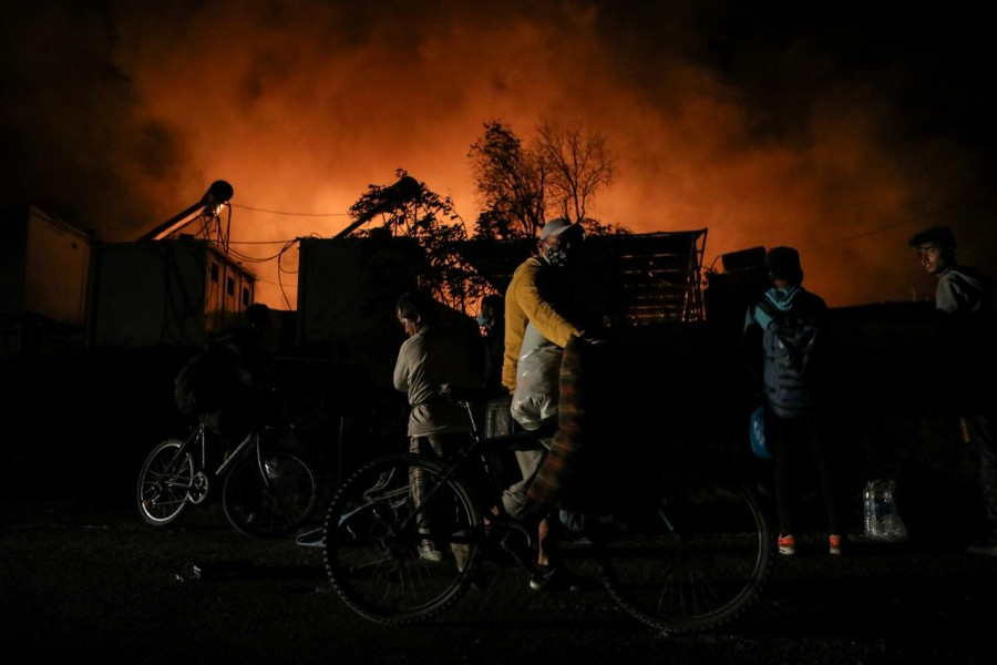 Refugees and migrants carry their belongings as they flee from a fire burning at the Moria camp on the island of Lesbos, Greece, September 9, 2020. REUTERS/Elias Marcou