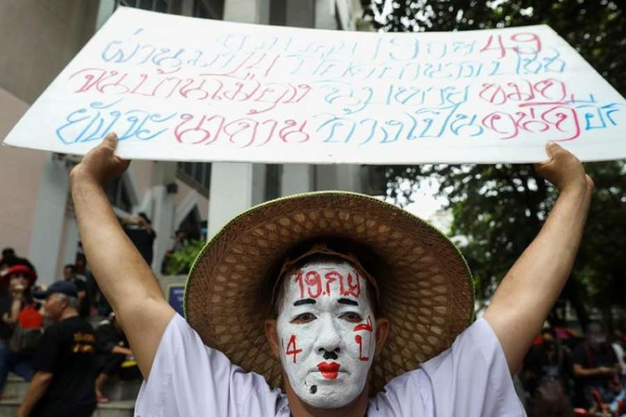 A pro-democracy protester with a painted face holding a placard as he attends a mass rally to call for the ouster of prime minister Prayuth Chan-ocha's government and reforms in the monarchy, in Bangkok, Thailand, on Saturday –Reuters Photo