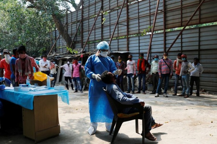 A healthcare worker wearing personal protective equipment (PPE) takes a swab from a migrant laborer for a rapid antigen test at the site of an under construction residential complex amidst a coronavirus disease (Covid-19) outbreak in New Delhi, India on September 19, 2020 — Reuters photo