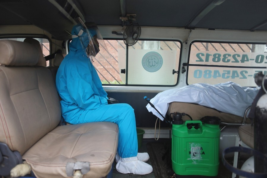 A healthcare worker, wearing protective suits, sits inside an ambulance that carrying the dead body of a victim who died with Covid-19 symptoms in Dhaka — File photo