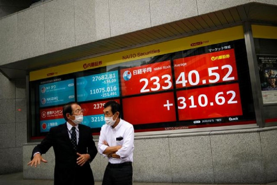 Men wearing protective face masks chat in front of a screen displaying Nikkei share average and world stock indexes outside a brokerage, amid the coronavirus disease (Covid-19) outbreak, in Tokyo, Japan, October 5, 2020 -- Reuters