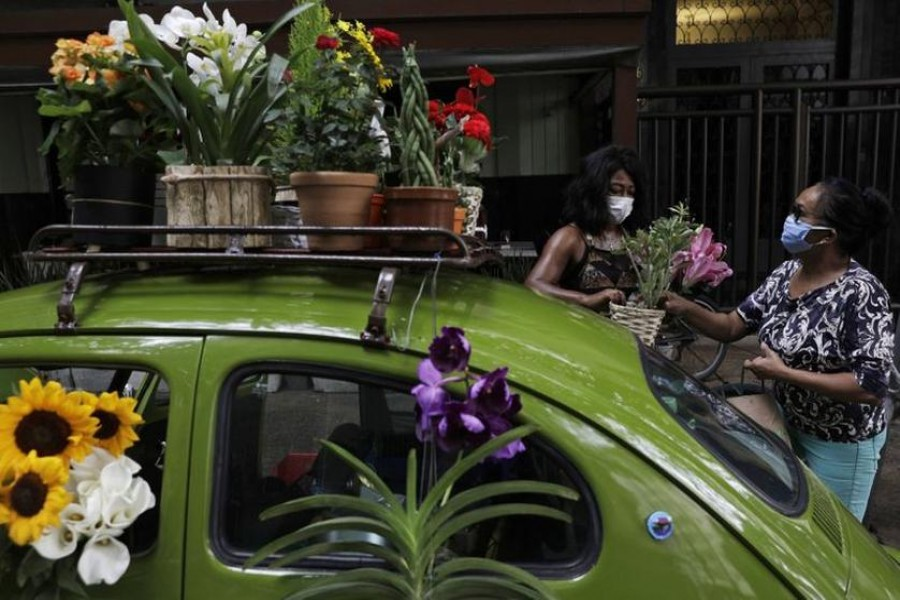Valcineia Machado, also known as Roberta, sells flowers to a customer next to her car which she transformed to a mobile flower shop after loosing her business amid the coronavirus disease (Covid-19) outbreak, in Rio de Janeiro, Brazil on October 8, 2020 — Reuters photo