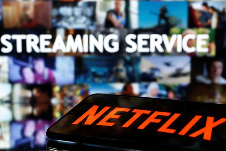 """A smartphone with the Netflix logo lies in front of displayed """"Streaming service"""" words in this illustration taken on March 24, 2020 — Reuters/Files"""