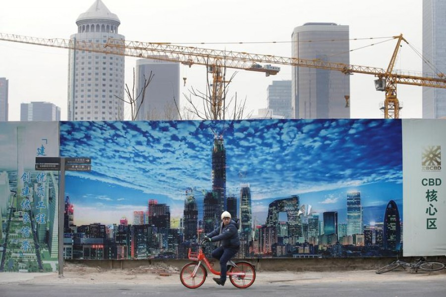 A man cycles outside the construction sites in Beijing's central business area, China, January 18, 2019 — Reuters/Files