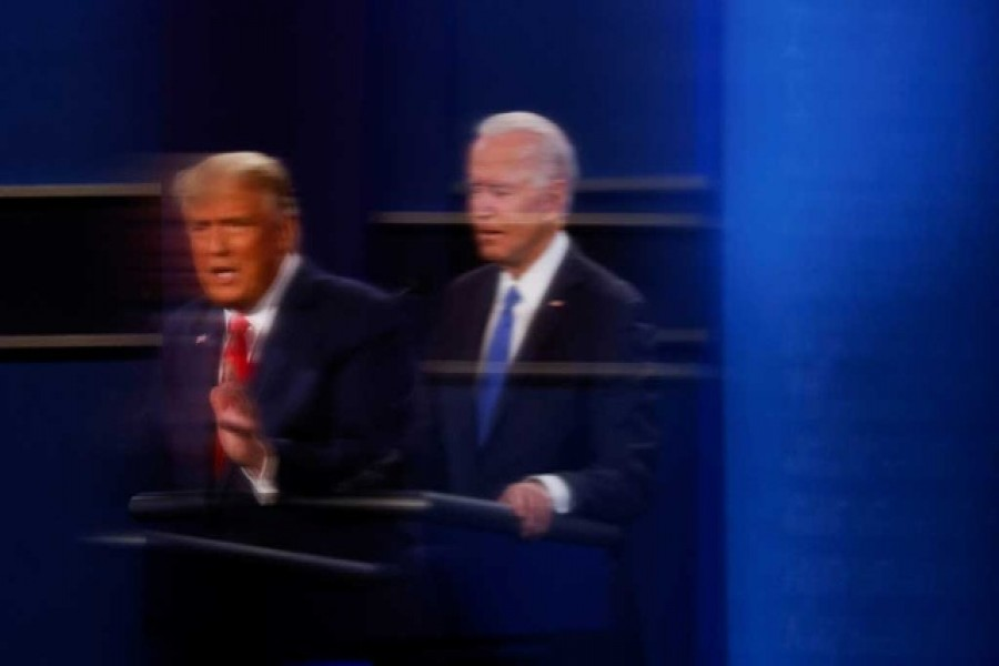 US President Donald Trump and Democratic presidential nominee Joe Biden are reflected in the plexiglass protecting a tv camera operator from Covid as they participate in their second 2020 presidential campaign debate at Belmont University in Nashville, Tennessee, US, October 22, 2020 — Reuters