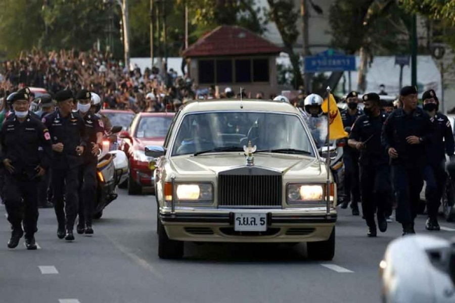 The royal motorcade carrying Thailand's Queen Suthida and Prince Dipangkorn drives past a group of anti-government demonstrators in front of Government House, on the 47th anniversary of the 1973 student uprising, in Bangkok, Thailand October 14, 2020. Picture taken October 14, 2020. REUTERS