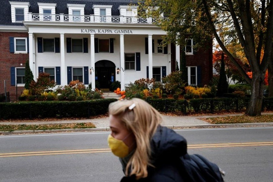 A woman wearing a protective face mask walks past a sorority house on the University of Michigan campus, where state health officials in Michigan issued a stay-in-place order for undergraduate students, in Ann Arbor, Michigan, US, October 26, 2020 — Reuters