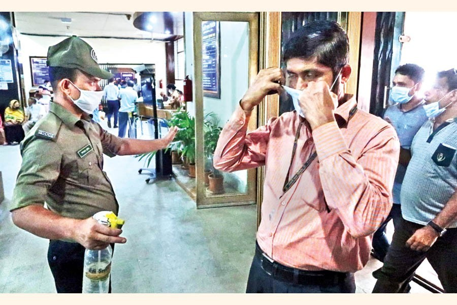 With 'No mask, no service' policy in effect at all offices, a security guard makes a person wear his mask before he enters the Sonali Bank at Motijheel in the city on Tuesday — FE photo by Shafiqul Alam