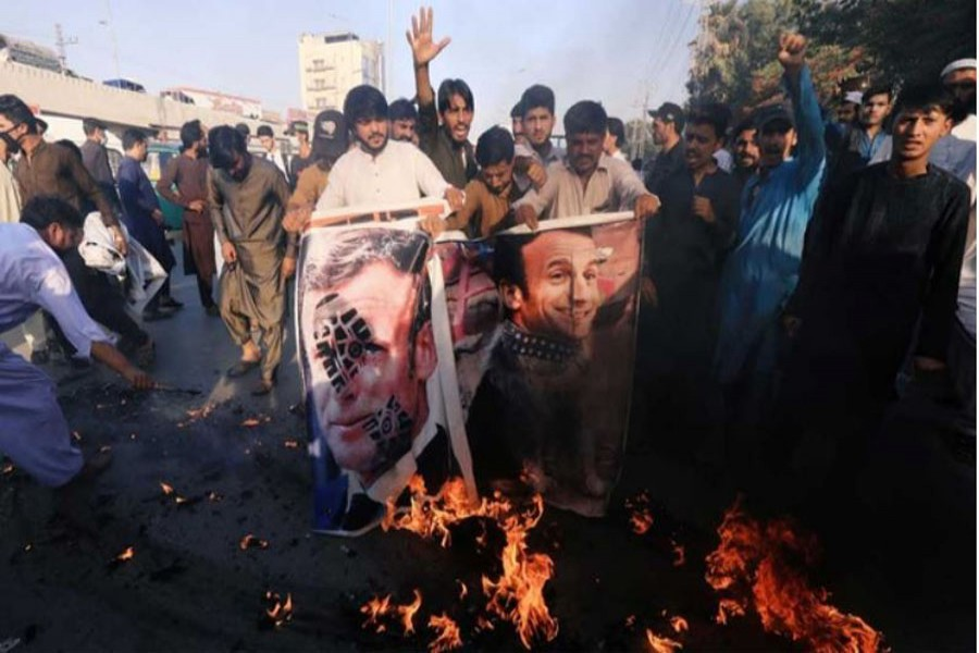 People chant slogans as they set fire to a banner with an image of French President Emmanuel Macron during a protest against cartoon publications of Prophet Mohammad in France and French President Emmanuel Macron's comments, in Peshawar, Pakistan Oct 27, 2020. REUTERS