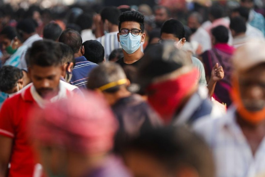 A man wearing a protective mask is seen among people at a crowded market amidst the spread of the coronavirus disease (Covid-19) in Mumbai, India on October 29, 2020 — Reuters photo