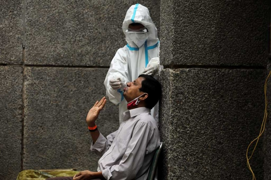 A healthcare worker wearing personal protective equipment (PPE) collects a swab sample from a man amidst the spread of the coronavirus disease (Covid-19), at a testing center in New Delhi, India on October 29, 2020 — Reuters photo