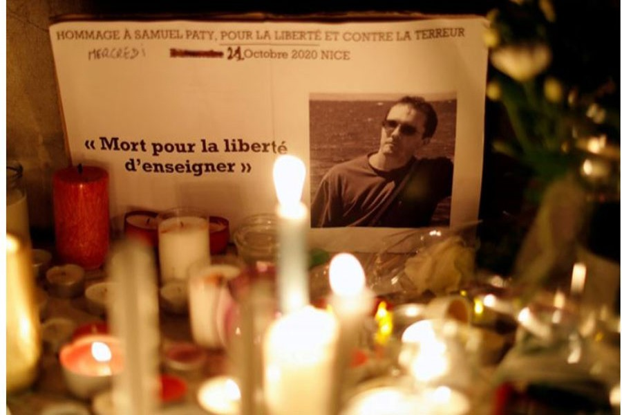Candles are lit at a makeshift memorial as people gather to pay homage to Samuel Paty, the French teacher who was beheaded on the streets of the Paris suburb of Conflans-Sainte-Honorine, as part of a national tribute, in Nice, France, October 21, 2020. Reuters