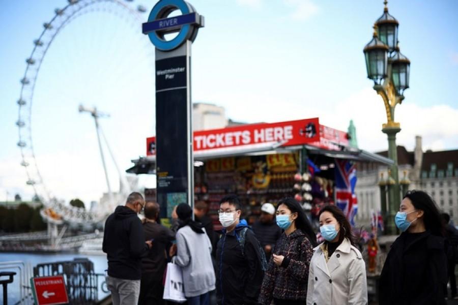 People wearing protective face masks walk across Westminster Bridge, during the coronavirus disease (COVID-19) outbreak, in London, Britain, October 22, 2020. Reuters