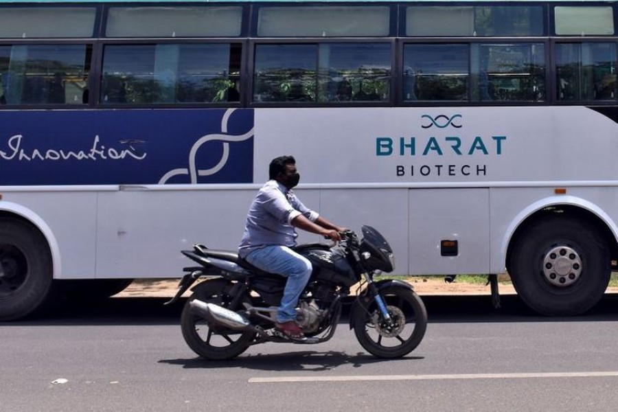 A man rides his motorcycle past a parked bus of Indian biotechnology company Bharat Biotech outside its office in Hyderabad, India on July 3, 2020 — Reuters/Stringer/Files