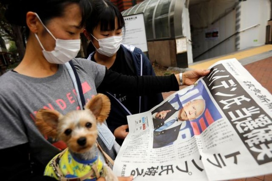 People read an extra edition of a newspaper reporting that Democratic US presidential nominee Joe Biden is projected to win the 2020 US presidential election, in Tokyo, Japan, November 8, 2020 — Reuters