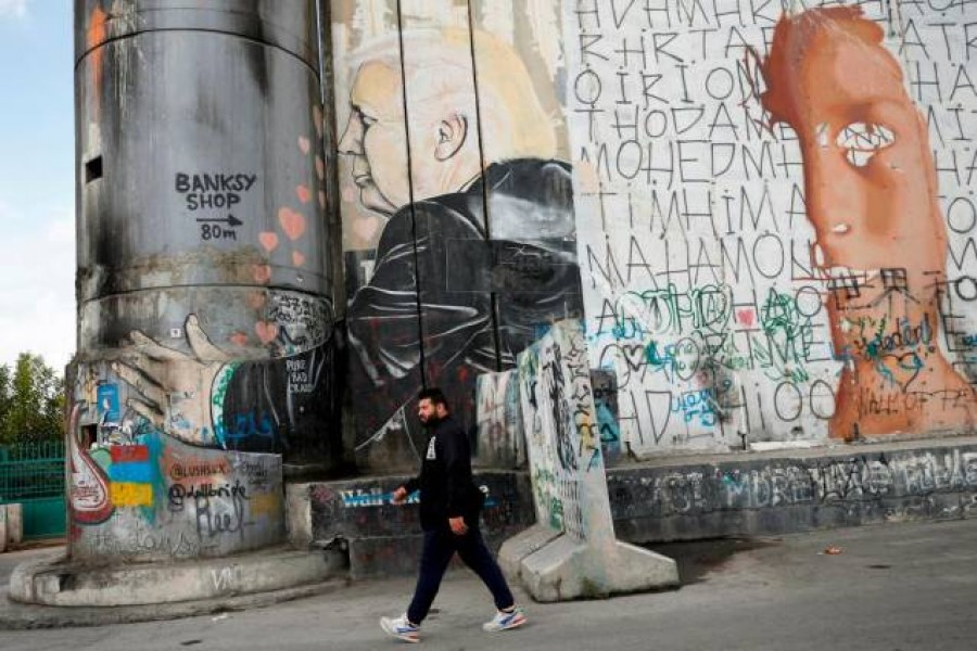 A Palestinian man walks past an anti-US President Donald Trump mural which was painted on a section of the Israeli barrier, in Bethlehem in the Israeli-occupied West Bank November 2, 2020. — Reuters