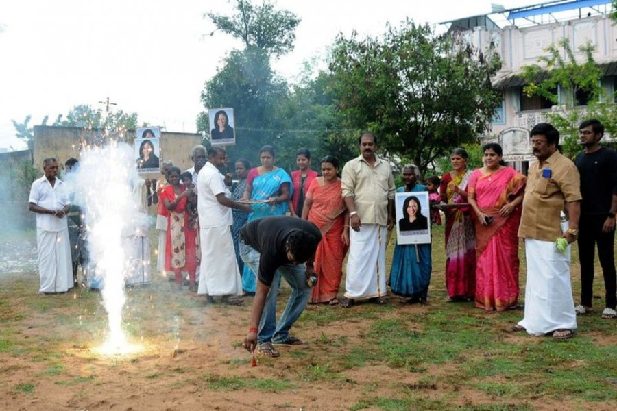 A man lights fireworks as villagers gather to celebrate the victory of US Vice President-elect Kamala Harris in Painganadu near the village of Thulasendrapuram, where Harris' maternal grandfather was born and grew up, in the southern state of Tamil Nadu, India, November 8, 2020. REUTERS/Stringer