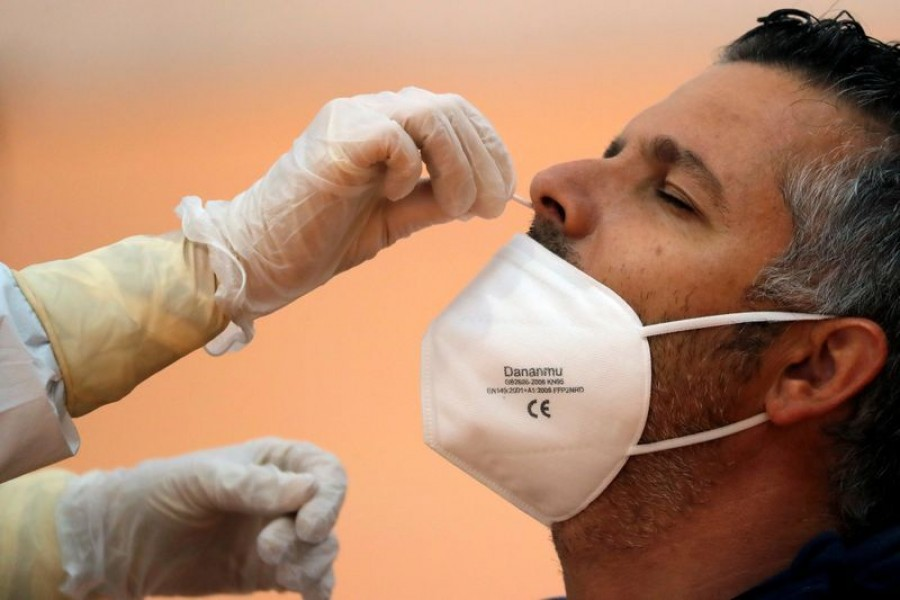 FILE PHOTO: A healthcare worker takes a swab sample from a man to be tested for the coronavirus disease (COVID-19) during a massive test in the small Andalusian village of Arriate, Spain November 7, 2020. REUTERS/Jon Nazca/File Photo