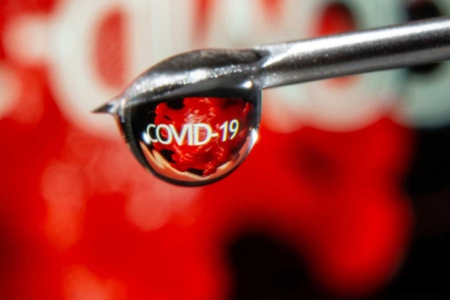 """The word """"COVID-19"""" is reflected in a drop on a syringe needle in this illustration taken November 9, 2020. REUTERS"""