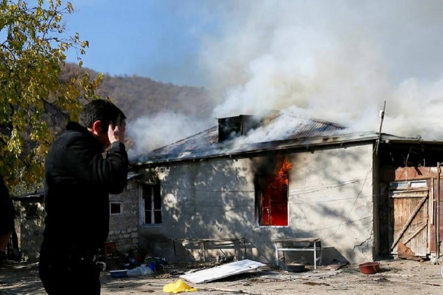 A man reacts as he stands near a house set on fire by departing Ethnic Armenians, in an area which had held under their military control but is soon to be turned over to Azerbaijan, in the village of Cherektar in the region of Nagorno-Karabakh, November 14, 2020 — Reuters