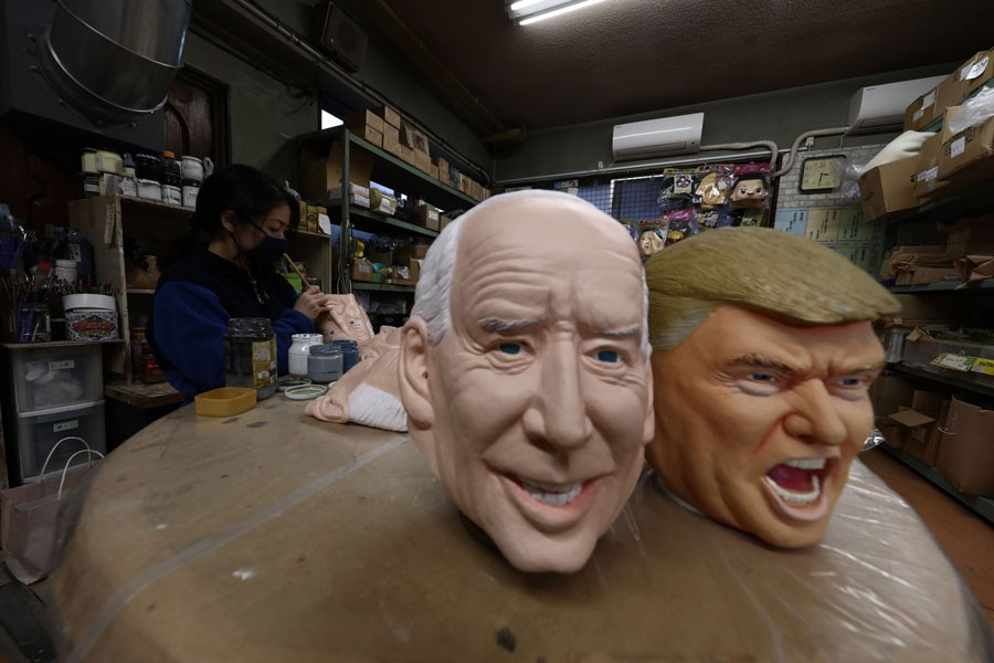 An employee works next to masks of US President-elect Joe Biden (L) and US President Donald Trump at the Ogawa Studios mask factory in Saitama, north of Tokyo on November 12, 2020. —AFP