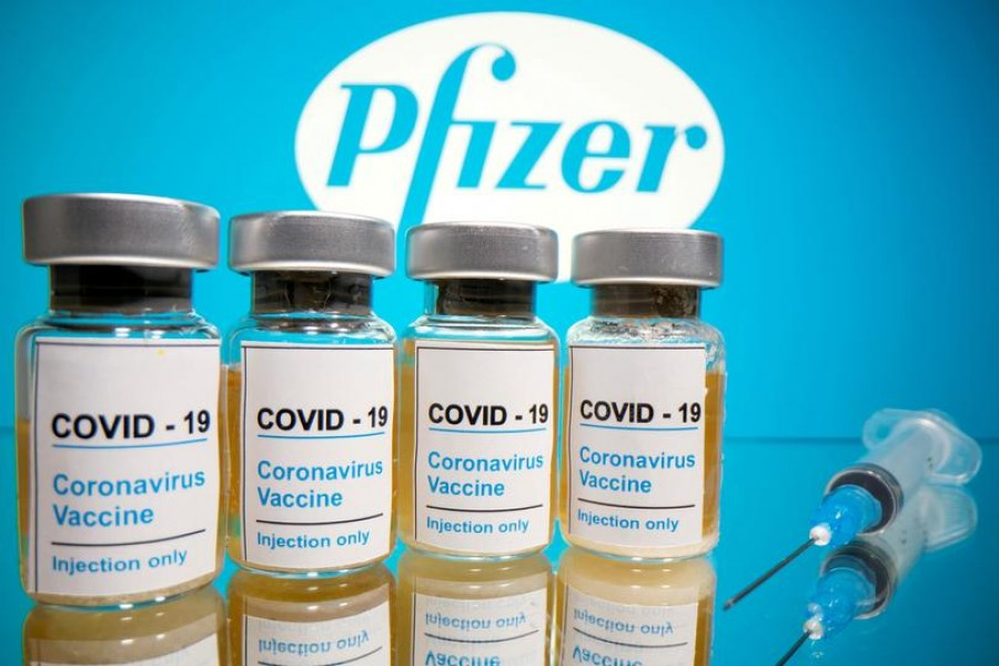 "Vials with a sticker reading, ""COVID-19 / Coronavirus vaccine / Injection only"" and a medical syringe are seen in front of a displayed Pfizer logo in this illustration taken on October 31, 2020 — Reuters/Files"
