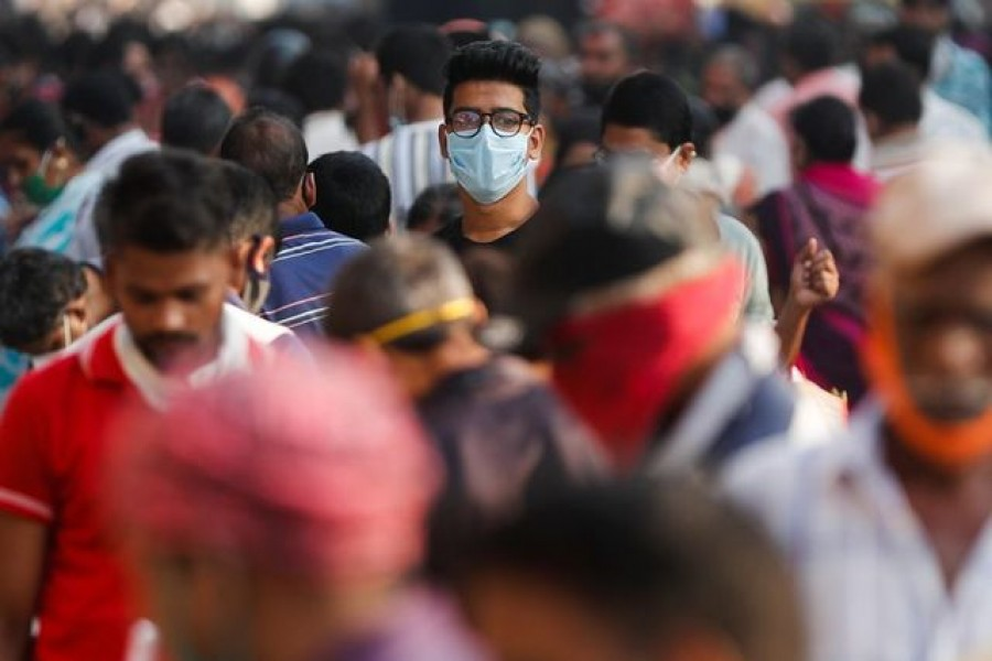 A man wearing a protective mask is seen among people at a crowded market amidst the spread of the coronavirus disease (Covid-19) in Mumbai, India, on October 29, 2020 — Reuters/Files