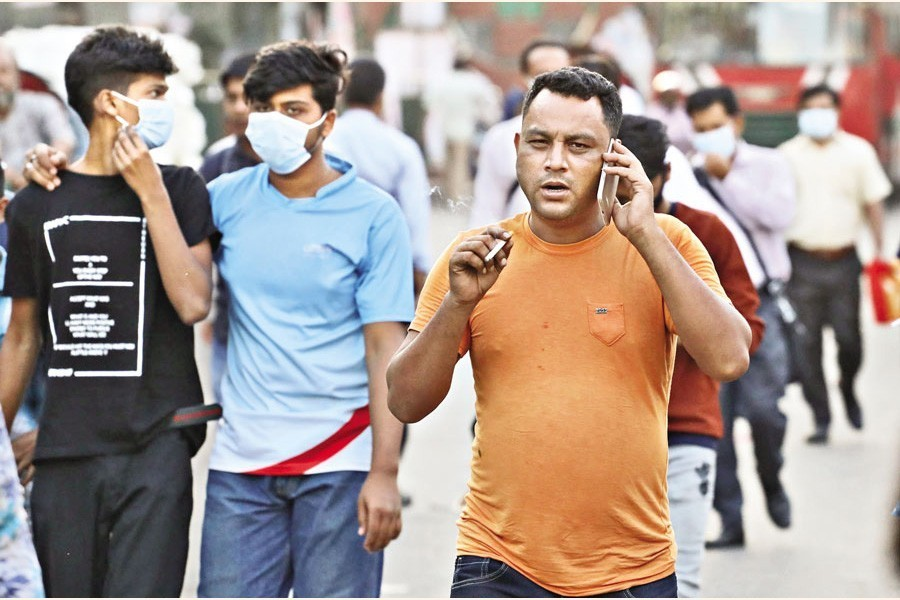 A pedestrian with no mask on his face is seen smoking in a public place unaware of the legal bars prohibiting both. The photo was taken at Bangabandhu Avenue in the city — FE Photo by Shafiqul Alam
