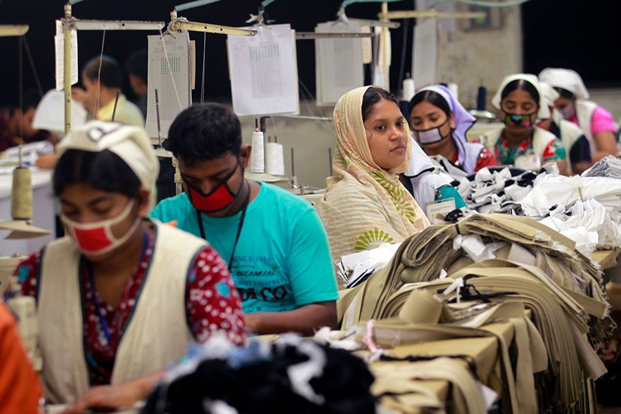 Women work at a garment factory inside the Dhaka Export Processing Zone (DEPZ) in Savar, April 11, 2013 – Reuters/Files