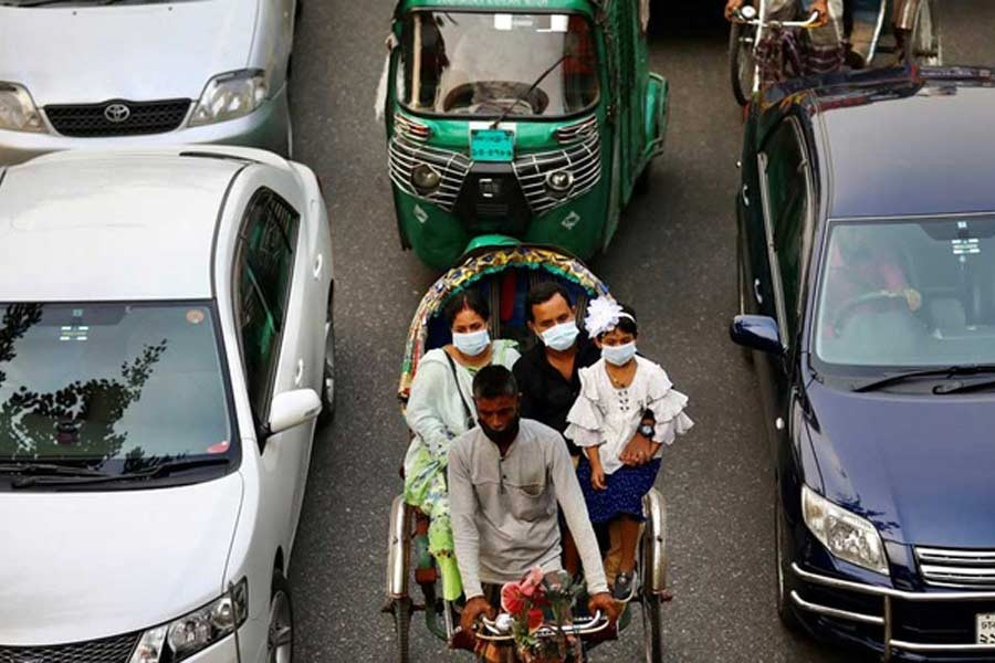 People wearing protective masks while riding on a rickshaw in Dhaka. The photo was taken on November 19. –Reuters file photo