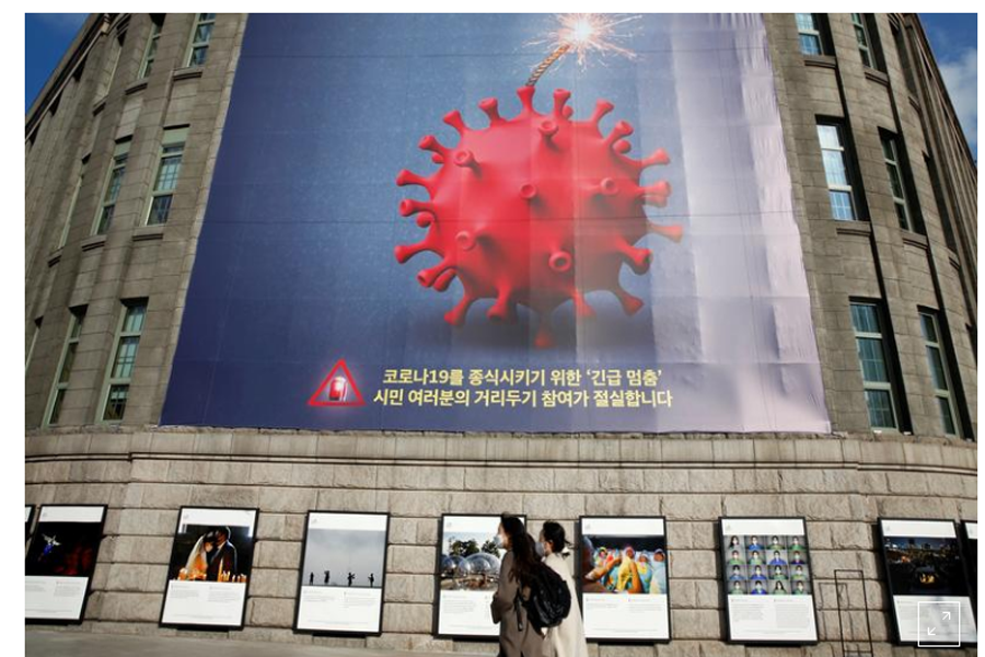 FILE PHOTO: Women wearing face masks walk past a banner promoting a social distancing campaign displayed on the wall of Seoul City Hall in Seoul, South Korea, November 27, 2020. REUTERS/Heo Ran