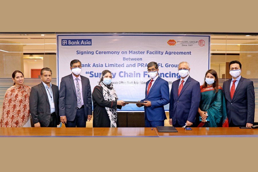 Mr Md Arfan Ali (fourth from right), President & Managing Director of Bank Asia Ltd and Ms Uzma Chowdhury (fourth from left), Director of PRAN-RFL Group seen exchanging documents on behalf of their respective organisations