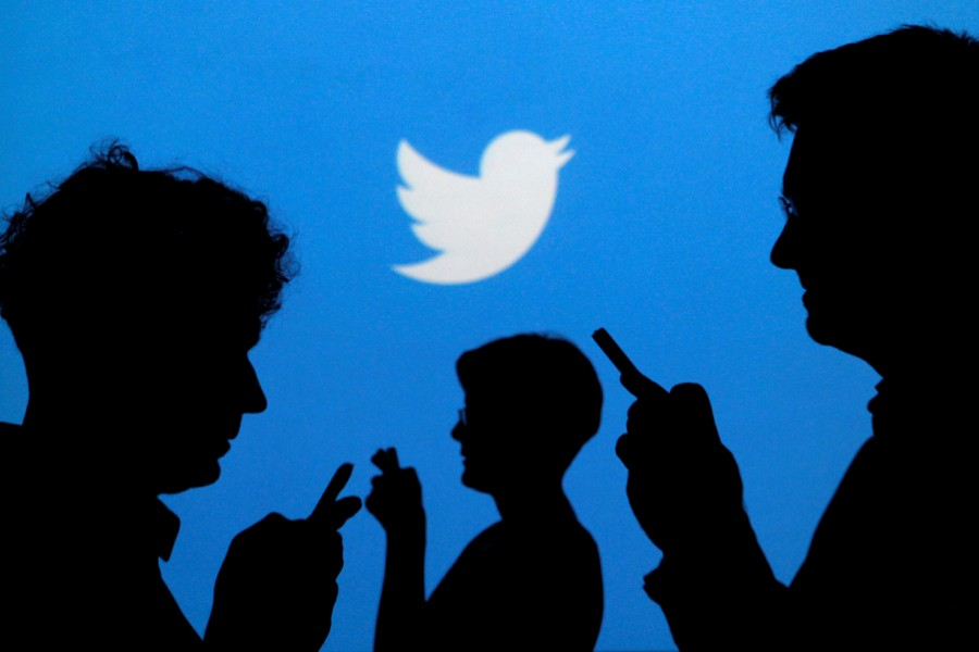 People holding mobile phones are silhouetted against a backdrop projected with the Twitter logo in this illustration picture taken on September 27, 2013 — Reuters/Files