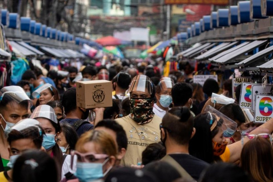 FILE PHOTO: Filipinos wearing masks and face shields for protection against the coronavirus disease (COVID-19) walk along a street market in Manila, Philippines, December 3, 2020. REUTERS/Eloisa Lopez/File Photo