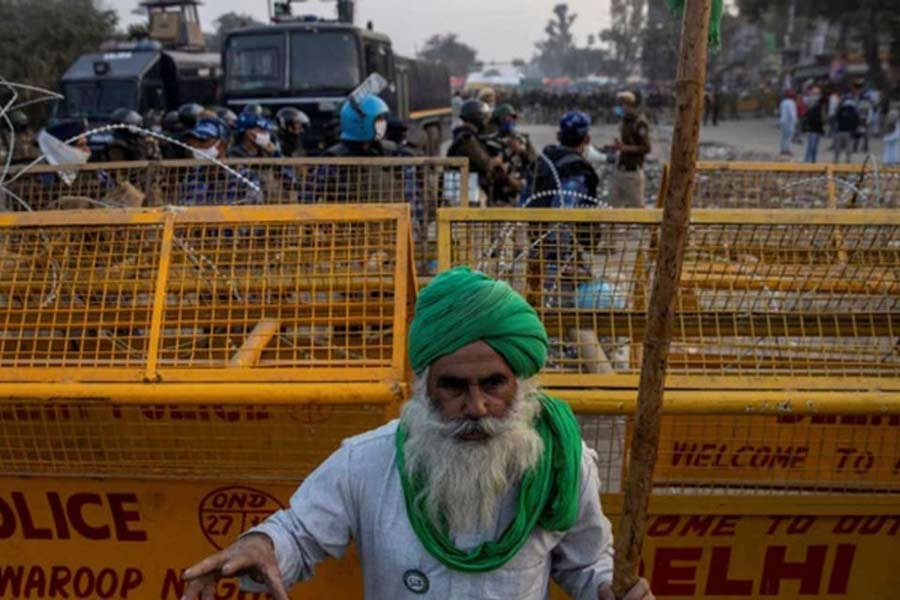 A farmer standing in front of police barricades during a protest against the newly passed farm bills at Singhu border near Delhi on Thursday –Reuters file photo