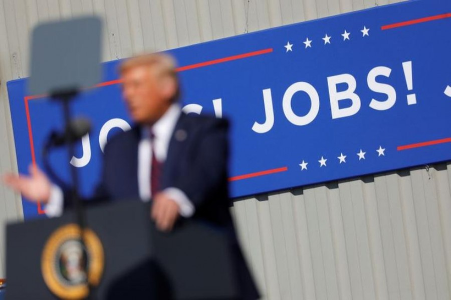"""US President Donald Trump speaks in front of a """"JOBS! JOBS! JOBS!"""" banner at a Trump re-election campaign event at Mariotti Building Products in Old Forge, Pennsylvania, US, August 20, 2020. REUTERS/Tom Brenner/Files"""