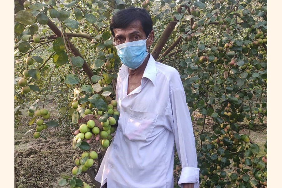 A hearing-impaired farmer, Hossain Sardar posing at his plum garden in Khulna's Dumuria — FE Photo