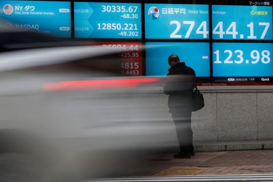 A man stands in front of a screen displaying Nikkei share average and the world's stock indexes outside a brokerage, amid the coronavirus disease (Covid-19) outbreak, in Tokyo, Japan on December 30, 2020 — Reuters/Files