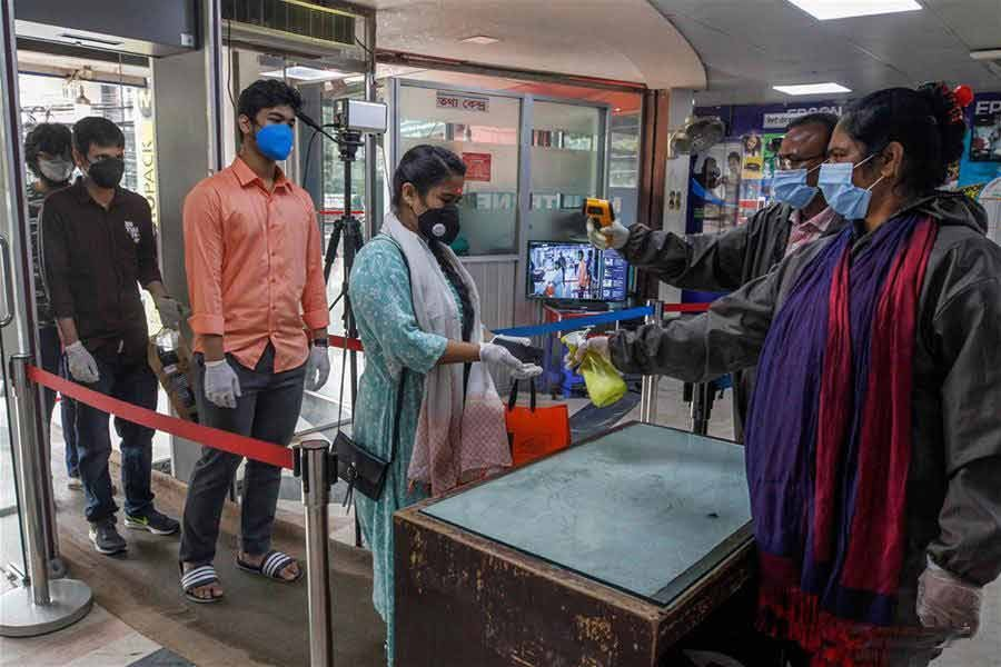 People have their temperature checked while entering a market in Dhaka, Bangladesh on May last    —Xinhua