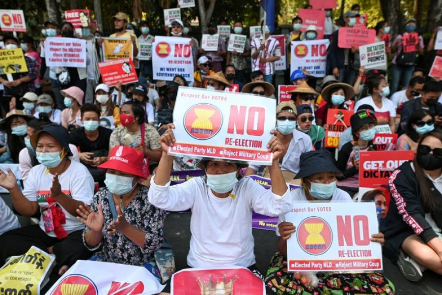 FILE PHOTO: Demonstrators hold placards during a rally against the military coup in front of Indonesian embassy in Yangon, Myanmar, February 24, 2021. REUTERS/Stringer