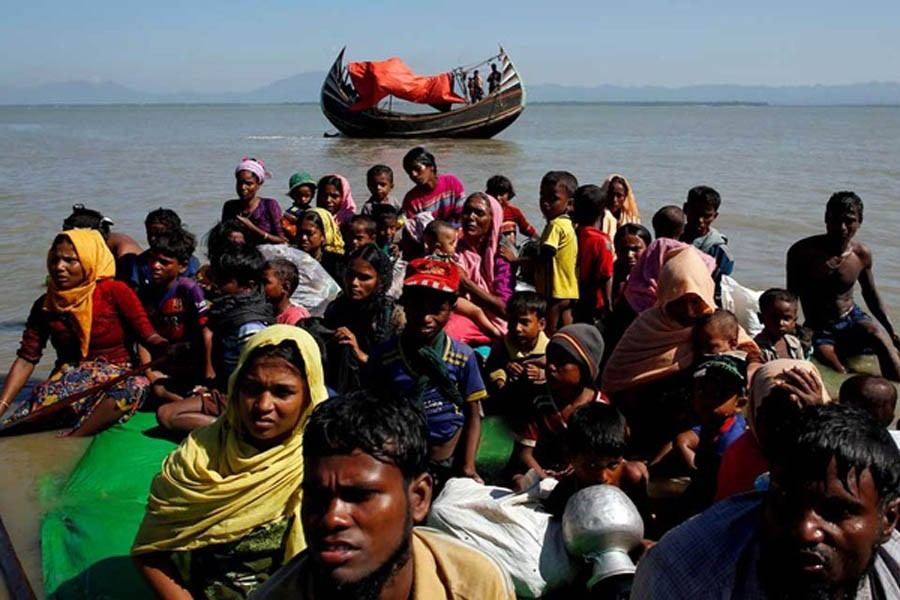 Rohingya refugees sit on a makeshift boat as they get interrogated by the Border Guard Bangladesh after crossing the Bangladesh-Myanmar border, at Shah Porir Dwip near Cox's Bazar, Bangladesh November 9, 2017. REUTERS