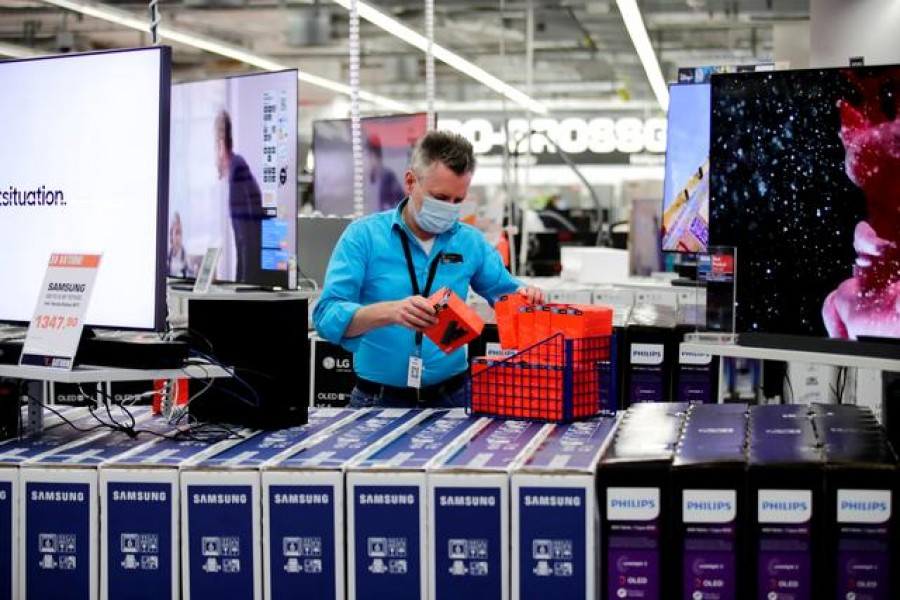 FILE PHOTO: An employee wearing a protective mask works at a Saturn electronic store as the coronavirus disease (COVID-19) lockdown measures are eased in Berlin, Germany, March 11, 2021. REUTERS/Hannibal Hanschke