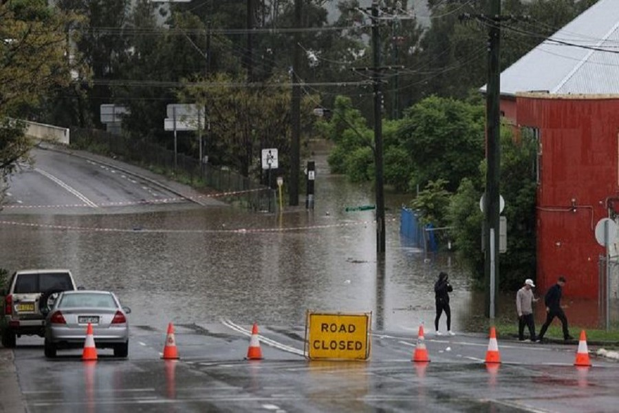 People walk on a street inundated with floodwaters in the suburb of Windsor as the state of New South Wales experiences widespread flooding and severe weather, in Sydney, Australia, March 22, 2021 — Reuters