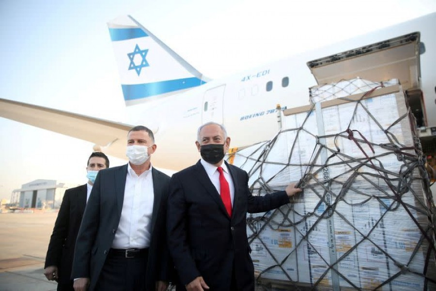 Israel Prime Minister Benjamin Netanyahu and Health Minister Yuli Edelstein attend the arrival of a plane with a shipment of Pfizer-BioNTech coronavirus disease (Covid -19) vaccines, at Ben Gurion airport, near the city of Lod, Israel, January 10, 2021. Motti Millrod/Pool via Reuters
