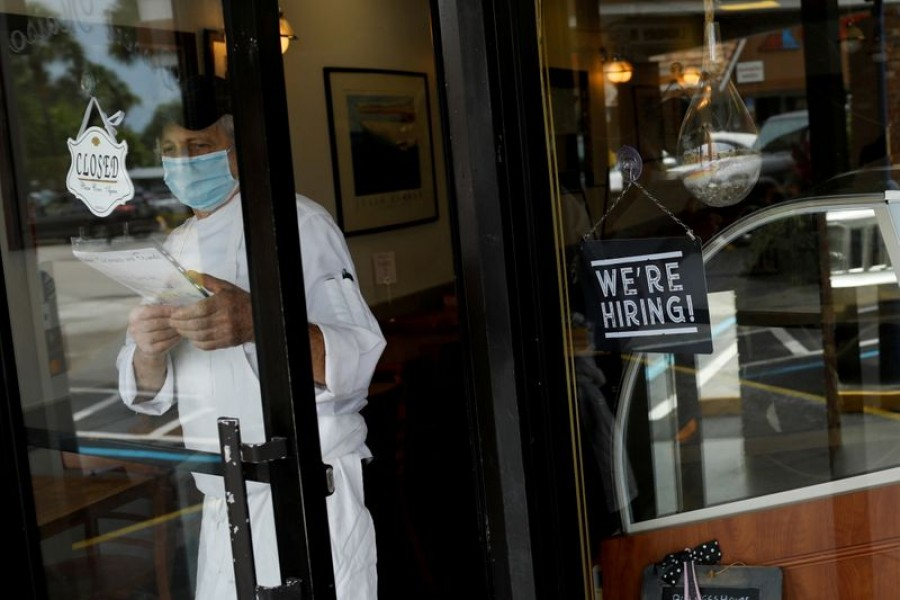 """A """"We're Hiring"""" sign advertising jobs is seen at the entrance of a restaurant, as Miami-Dade County eases some of the lockdown measures put in place during the coronavirus disease (Covid-19) outbreak, in Miami, Florida, US on May 18, 2020 — Reuters/Files"""