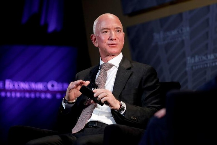 "FILE PHOTO: Jeff Bezos, president and CEO of Amazon and owner of The Washington Post, speaks at the Economic Club of Washington DC's ""Milestone Celebration Dinner"" in Washington, US, September 13, 2018. REUTERS/Joshua Roberts/File Photo"