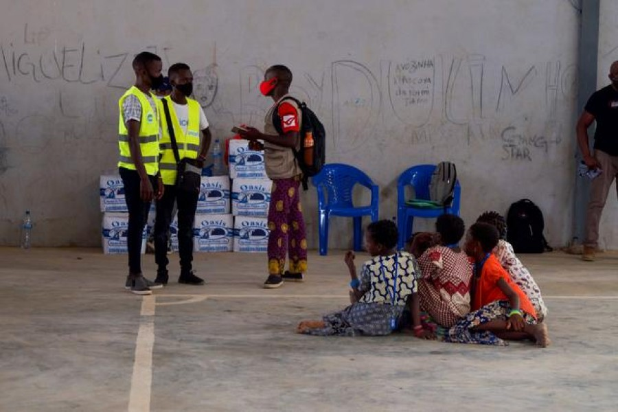 People, who fled an attack claimed by Islamic State-linked insurgents on the town of Palma, look on as aid workers consult a person at a displacement centre in Pemba, Mozambique, April 2, 2021. REUTERS/Emidio Jozine