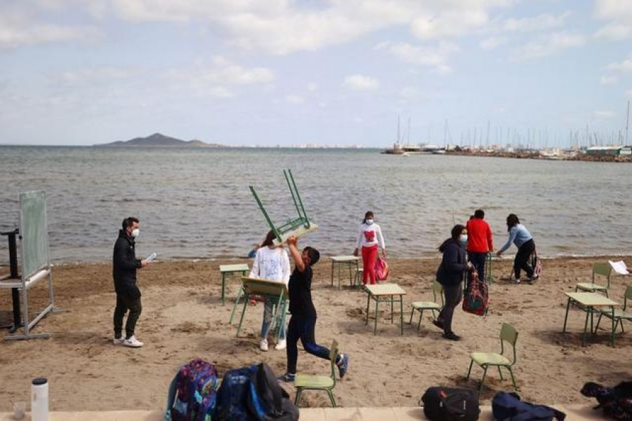 FILE PHOTO: Students and teachers of the Felix Rodriguez de la Fuente school remove chairs and tables at the end of their class, as part of a project known as 'Aire Limpio' (Fresh Air) at the Playa de los Nietos (The Grandchildren's Beach), which aims to use better air quality for children during the coronavirus disease (COVID-19) pandemic, near Cartagena, southern Spain April 8, 2021. REUTERS/Nacho Doce
