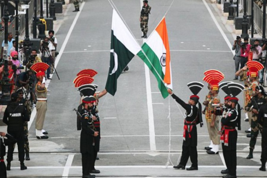Pakistani Rangers (wearing black uniforms) and Indian Border Security Force (BSF) officers lower their national flags during parade on the Pakistan's 72nd Independence Day, at the Pakistan-India joint check-post at Wagah border, near Lahore, Pakistan on August 14, 2019 — Reuters/Files